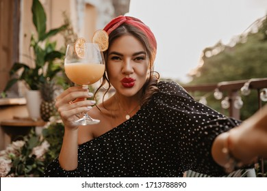Beautiful charming girl with curly hair, bright lips and silver accessories in stylish black blouse looking into camera and holding cocktail..