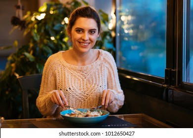 Beautiful charming girl having dinner at cafe, using cutlery for eating salad, looking at camera. Dressed in knitted sweater.