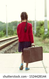 Beautiful charming little girl with pigtails waiting for train at station dressed dark blue dress with flowers and red blouse holding big vintage luggage. Young traveler, retro stylization.