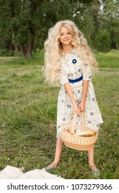 Beautiful charming long curly blonde hair teenage girl wearing a long light dress outdoors on a picnic smiles and holds a big basket full of food and a bottle of milk. Copy space. Lifestyle