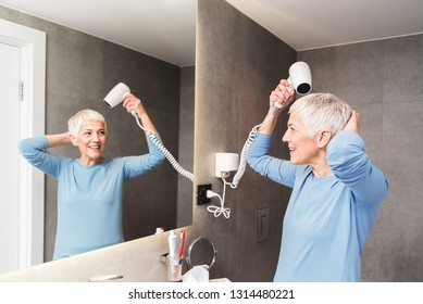 Beautiful charming mature woman full of energy with gorgeous smile drying her short gray hair with blowdryer in her bathroom and looking at mirror