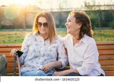 Beautiful charming smiling girlfriends middle-aged mature women sit on a bench in the park in the sun and chat
