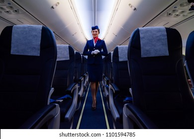 Beautiful charming Stewardess dressed in blue uniform staying on the Aisle inside the plane in airport. Smiling cabin crew. St.Petersburg, Russia - 10 aug. 2017