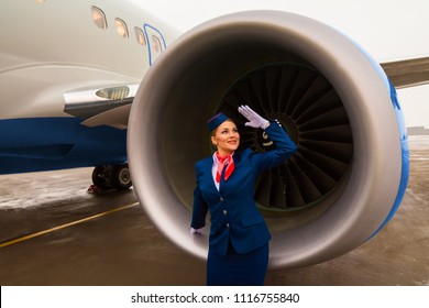 Beautiful charming Stewardess dressed in blue uniform staying near the engine of passenger plane in airport. Smiling cabin crew. St.Petersburg, Russia - 10 aug. 2017