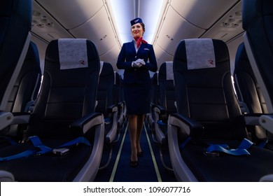 Beautiful charming Stewardess dressed in official blue uniform of Rossiya Russian airlines staying on the Aisle inside the plane in airport. Smiling cabin crew. St.Petersburg, Russia - 10 aug. 2017