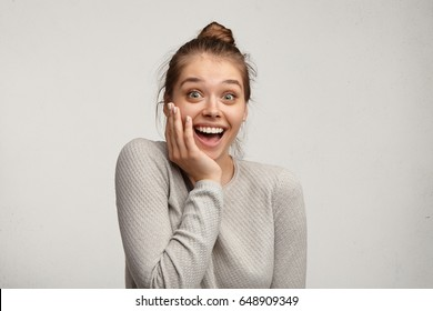 Beautiful charming young Caucasian 20 y.o. woman with hair knot opening mouth widely, saying Omg, Wow, having excited astonished look, holding hand on her face, delighted with unexpected gift