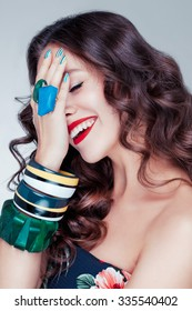 Beautiful charming young caucasian girl with brown chocolate hair, red lips, a lot of bracelets on her hands posing in studio. Happy mood.