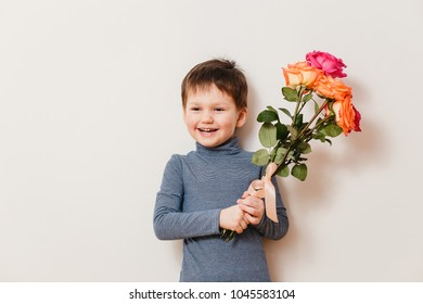 beautiful cheerful boy four years old with a bouquet of roses on a white background