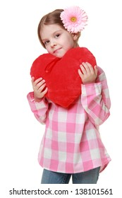 Beautiful cheerful child with beautiful hairstyle holds a big red heart on Holiday