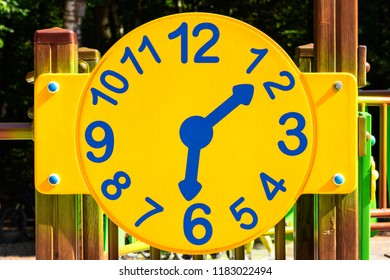 Beautiful, cheerful clock at the playground. Concept Childhood. Children's time. Xing yellow dial