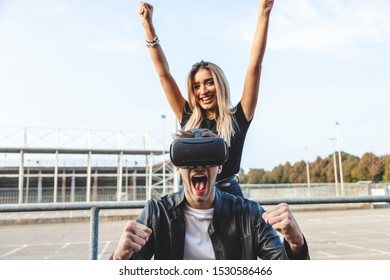 beautiful cheerful couple exulting in front of a stadium with virtual reality glasses.concept of technology addiction