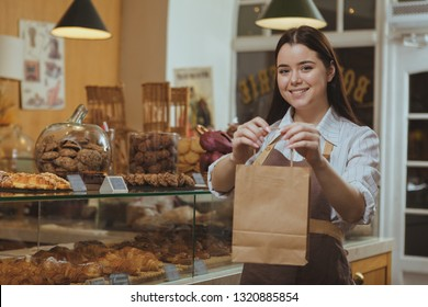 Beautiful cheerful female baker smiling, holding out paper shopping bag to the camera, working at her cafe. Lovely female confectioner selling delicous food at the bakery, copy space