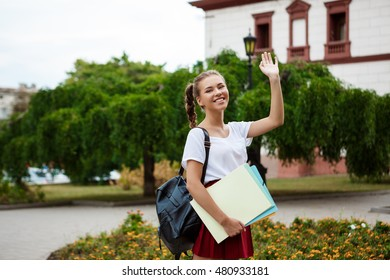 Beautiful cheerful female student smiling, greeting, holding folders outdoors, park background.