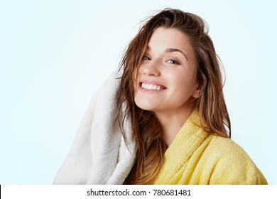 Beautiful cheerful female with wet dark hair wears bathrobe, holds towel, being glad to take shower and wash off all stess, isolated over white studio background. Smiling pleased woman in bathroom