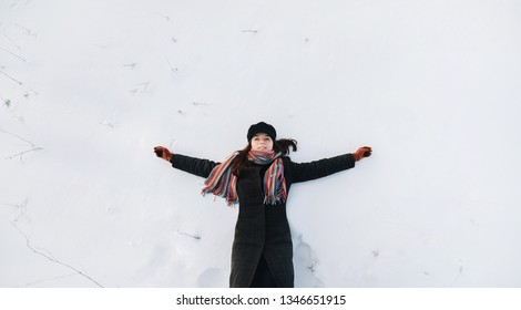 Beautiful and cheerful girl in black clothes lies in the winter on white snow, arms outstretched. Games and fun. Photography and nature, lifestyle. Top view, drone, joy.