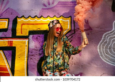 Beautiful cheerful girl in colorful stylish clothes with smoke flare, having fun time, standing near the wall with graffiti. Outdoors.
