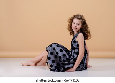 Beautiful cheerful girl with curly hair, portrait. Beautiful smile, bright dress.