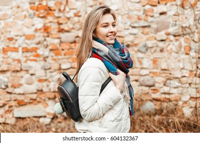 c3a917b083584 Beautiful cheerful girl with a cute smile in a white jacket and scarf with  a bag. fashion winter ...