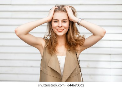 Beautiful cheerful girl smiling and enjoying near a wooden wall in a spring day