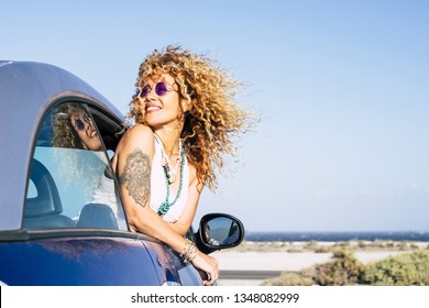 Beautiful cheerful happy caucasian woman outside the car with wind in curly long blonde hair - attractive people enjoying the freedom in outdoor coastline ocean vacation place