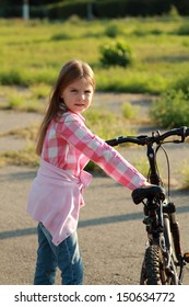 Beautiful cheerful little girl in sportswear riding a bicycle in a park in autumn day