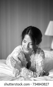 Beautiful cheerful pensive happy woman in nightie lies on the bed. Laugh. In the bedroom. Black and white.