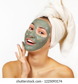 Beautiful cheerful teen girl applying facial clay mask. Beauty treatments, isolated over white background.