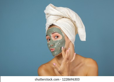 Beautiful cheerful teen girl applying facial clay mask. Beauty treatments, isolated on blue background.