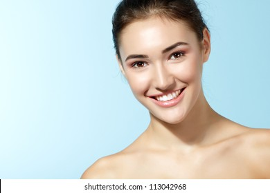 beautiful cheerful teen girl, beauty female face happy smiling and looking at camera over blue background