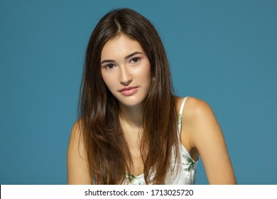 Beautiful cheerful teen girl looking at camera over blue background. Young charming woman posinng at studio.