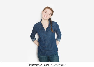 Beautiful cheerful teenage girl in a jeans shirt looking and smiling at camera on white background.