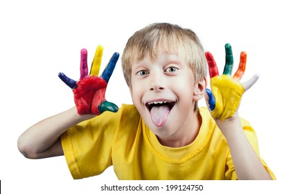 Beautiful cheerful white boy in yellow t-shirt showing painted hands with funny expression showing his tongue