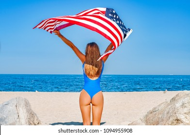 Beautiful cheerful woman holding an American flag on the beach. Travel. USA flag