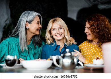 Beautiful cheerful women chatting and laughing in coffee house stock photo