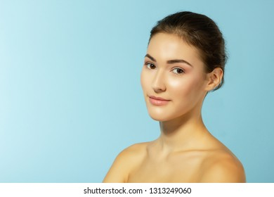 beautiful cheerful young woman, beauty female face happy smiling and looking at camera over blue background