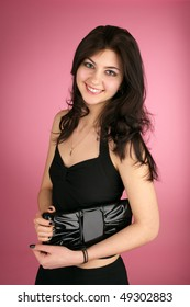 Beautiful cheerful young woman with handbag over pink background