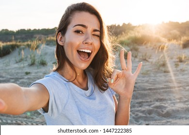Beautiful cheerful young woman having a good time at the beach on a lovely day, taking a selfie, showing ok gesture