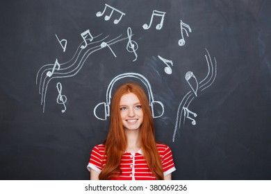 Beautiful cheerful young woman listening to music in earphones  drawn on chalkboard background