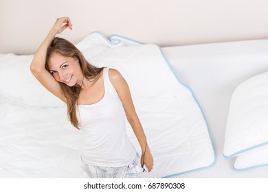 Beautiful cheerful young woman listening to the music, wearing pajamas and a headphones, dancing and jumping on the bed after waking up in the morning