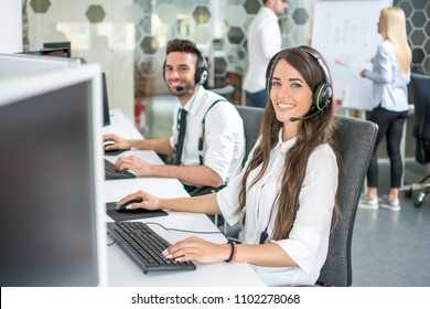 Beautiful and cheerful young woman and man telephone operators with headsets working on desktop computer in customer service call support helpline business center