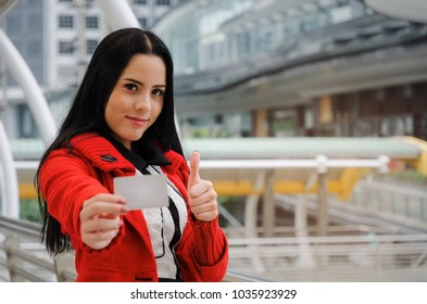 beautiful cheerful young woman in red jacket holding credit card and showing thumbs up in modern big city, fashion, promotion, special offer, winter sale, people, payment, shopping online concept