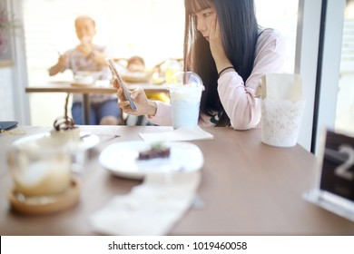 Beautiful chic cute Asian woman look down on smart phone in hand at coffee shop with blue color milk ice unicorn beverage plastic glass on wood table in alone valentine day.