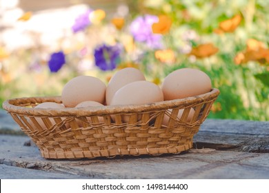 Beautiful chicken eggs in a wicker basket on a wooden Board against a landscape of greenery and flowers.