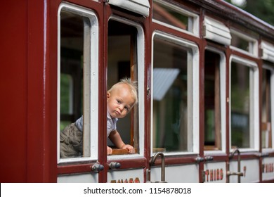 Beautiful child, baby boy, dressed in vintage clothes, enjoying old steam train on a hot summer day in England