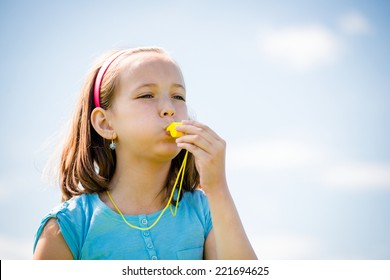 Beautiful child blowing in whistle - outdoor with blue sky