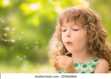 Beautiful child with dandelion flower in spring park. Happy kid having fun outdoors
