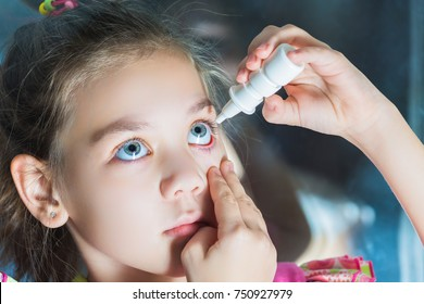 Beautiful child dripping in eye drops conjunctivitis.