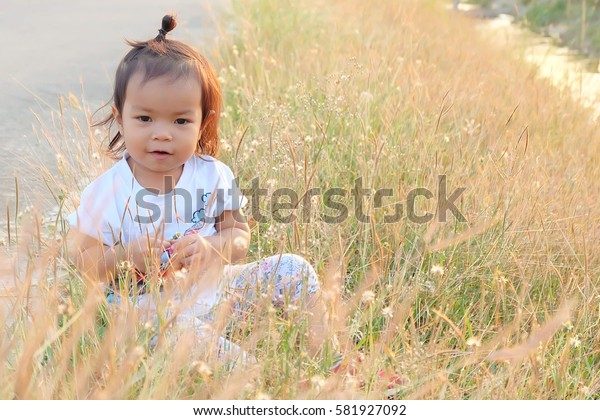 Beautiful child with flower in spring park. Happy kid having fun outdoors.