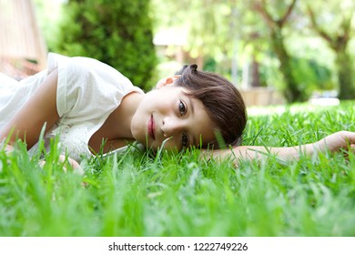 Beautiful child girl laying on green grass in sunny park, looking smiling, enjoying nature outdoors. Healthy female kid relaxing in nature, wellness leisure recreation lifestyle.