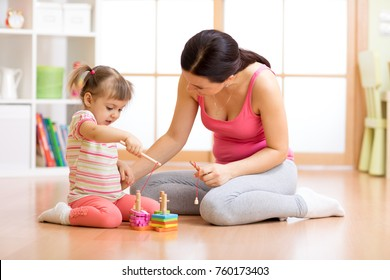 Beautiful child girl playing with toys with mother or babysitter indoors